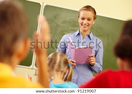 Portrait of smart teacher with exercise book looking at schoolkids in classroom