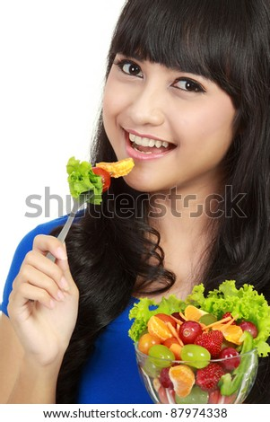 Portrait of smart young lady holding bowl of vegetable and fruit salad in white background