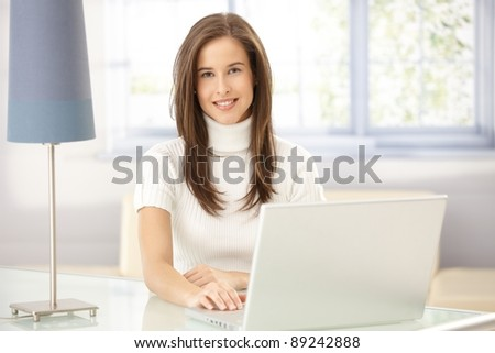 Portrait of smart young woman sitting at table in study, using laptop computer, looking at camera.?