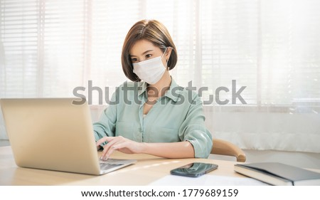 Portrait of sme business asian woman in wears medical protective mask working from home at the computer desktop. Self-isolation quarantine, new normal. Coronavirus outbreak and flu covid epidemic.