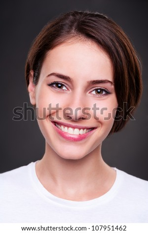 portrait of smiley cheerful woman over dark background. studio shot