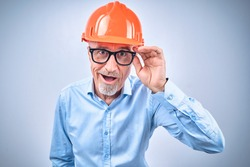 Portrait of smiling adult architect wearing hardhat and adjusting glasses, isolated on blue background. Building concept