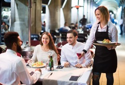 Portrait of smiling adult friends in outdoors restaurant and smiling waitress.  Focus on blonde girl