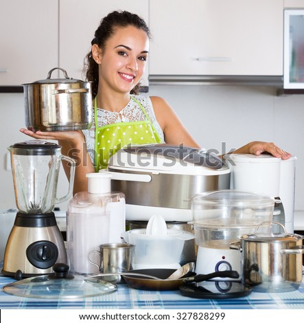 Portrait of smiling adult girl with kitchen appliances at home