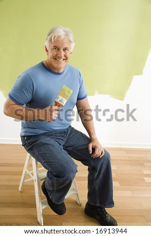 Portrait of smiling adult man sitting in front of half-painted wall with paintbrush.