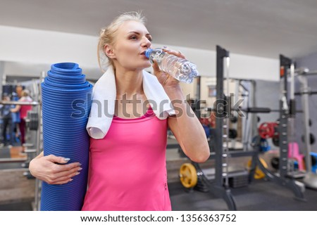 Portrait of smiling adult woman with bottle of water and sports mat in health club. Health fitness sport concept.