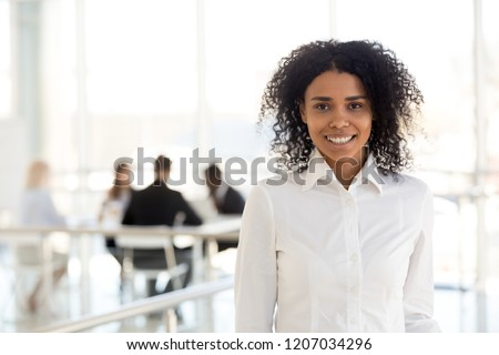 Portrait of smiling African American female employee posing in modern office building, happy black businesswoman or worker look at camera, making headshot picture in hallway or corridor