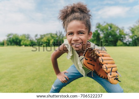 portrait of smiling african american little girl with baseball glove playing baseball in park