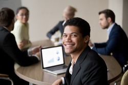Portrait of smiling African American male employee posing for picture during office business meeting with colleagues, happy black man worker shooting looking at camera busy at corporate briefing