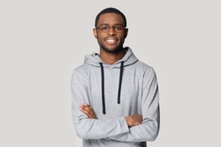 Portrait of smiling african American man in glasses and sportswear isolated on grey studio background pose for picture, happy black male in eyewear and hoodie stand with arms crossed look at camera