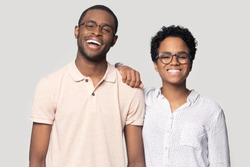 Portrait of smiling african American millennial couple in glasses stand isolated on grey studio background, happy ethnic black man and woman wear spectacles laugh posing together for picture