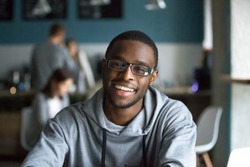 Portrait of smiling African American student looking at camera sitting in café, black millennial man posing making picture in coffeeshop, afro male in glasses drinking coffee working in coffeehouse
