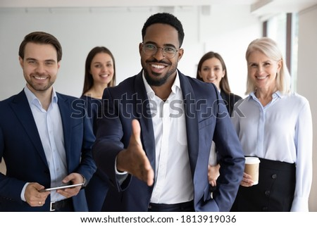 Portrait of smiling African American team leader stretch hand greeting job candidate or applicant in office. Happy multiracial businesspeople meet welcome newcomer at workplace. Employment concept. Stock photo ©