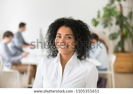 Portrait of smiling African American worker laughing looking at camera, black office employee posing for company business catalogue, having photo shoot at workplace, subordinates working at background