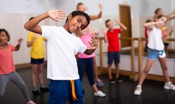 Portrait of smiling african boy showing dance elements during group class in dance center