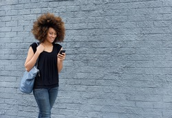 Portrait of smiling african woman walking with cell phone
