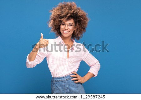 Portrait of smiling Afro American woman with bushy hair wearing fashionable eyeglasses, blue background.