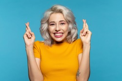 Portrait of smiling anticipating pretty female. Woman raised hands in hopeful gesture. Model posing in studio and looking at camera with joy and bit of fright. Isolated on blue