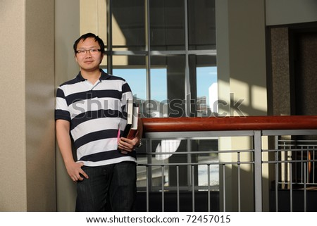 Portrait of smiling Asian student holding books indoors
