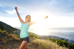 Portrait of smiling athletic woman with arms outstretched