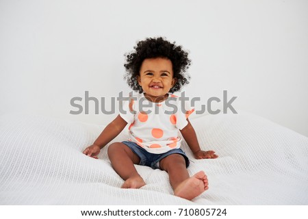 Portrait Of Smiling Baby Girl Sitting On Bed