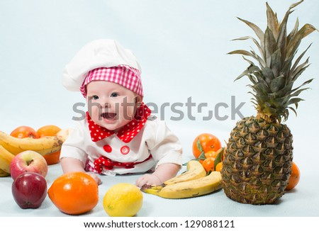 Portrait of smiling baby wearing a chef hat  surrounded by fruits. Use it for a child, healthy food concept
