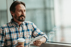 Portrait of smiling bearded male enjoying appetizing cup of coffee while using gadget indoor