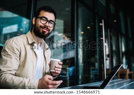 Portrait of smiling bearded millennial guy n eyewear for vision protection using gadgets wireless connection in coffee shop while studying online courses, prosperous male freelancer looking at camera Foto stock ©