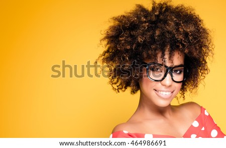 Portrait of smiling beautiful african american young woman. Girl with afro wearing eyeglasses. Yellow background. Studio shot.  #464986691