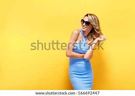 Portrait of smiling beautiful blonde girl in sunglasses and blue dress against of yellow background.Isolated