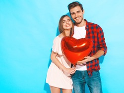 Portrait of Smiling Beautiful Girl and her Handsome Boyfriend holding  heart shaped air balloons and laughing. Happy  Family. Love. Happy Valentine's Day. Posing near blue wall