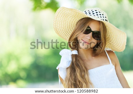 Portrait of smiling beautiful teenage in wide-brimmed hat and sunglasses, against green of summer park.