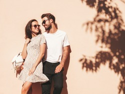 Portrait of smiling beautiful woman and her handsome boyfriend. Woman in casual summer clothes. Happy cheerful family. Female having fun. Couple posing in the street near wall in sunglasses
