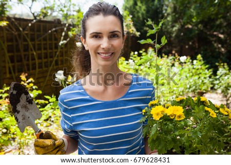 Portrait of smiling beautiful woman holding trowel and flowering pot at backyard on sunny day