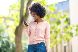 Portrait of smiling beautiful young black woman looking at mobile phone outside