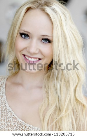 Portrait of smiling beautiful young blond woman