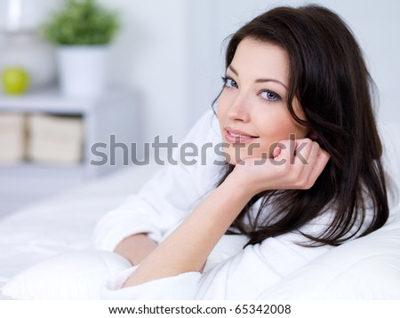 Portrait of smiling beautiful young brunette woman at home