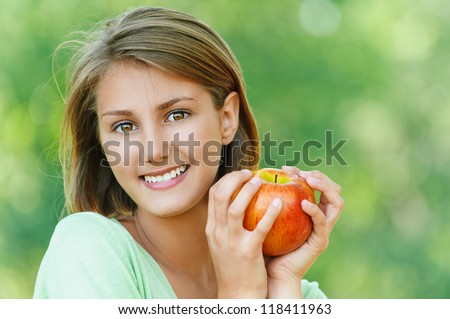 Portrait of smiling beautiful young woman close up with apple, against background of summer green park.