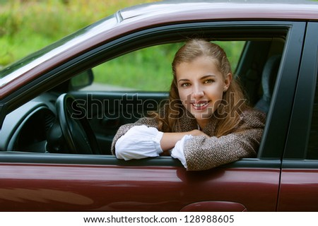 Portrait of smiling beautiful young woman-driver in car, against background of autumn park. - stock photo