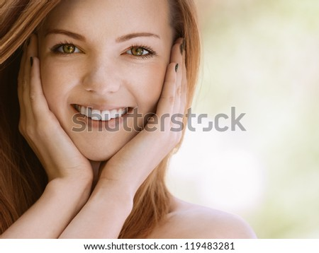 Portrait of smiling beautiful young woman with bare shoulders close up, against green of summer park.