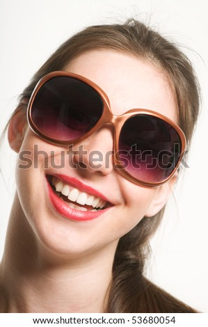 Portrait of smiling beautiful young woman with funy sunglasses
