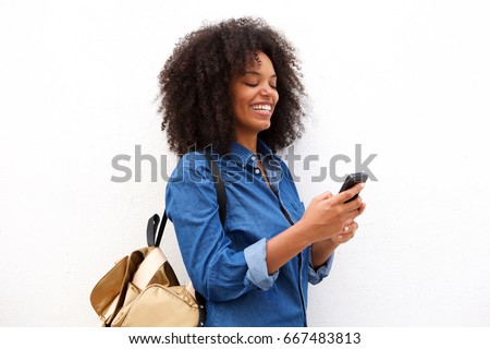Portrait of smiling black woman with smart phone and backpack #667483813