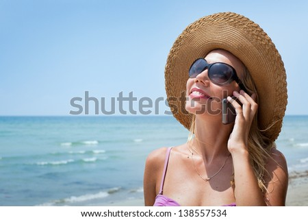 portrait of smiling blond woman with mobile phone on the beach