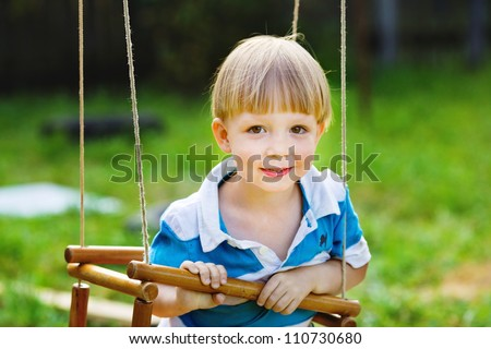 Portrait of smiling boy sitting on a swing, close up - stock photo