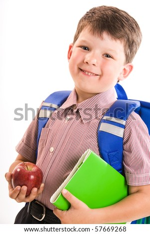 Portrait of smiling boy with apple and book ready to go to school