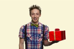 Portrait of smiling boy with bowtie holding a red gift box. Happy schoolboy with bowtie isolated on white background.