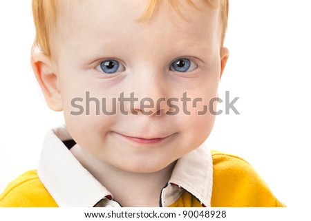 Portrait of smiling boy with red hair on a white background