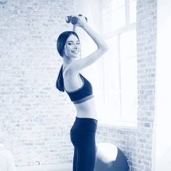 Portrait of smiling brunette girl in sportswear, doing fitness exercise with dumbbells, at home. Healthy lifestyle, weight lossing and sporting theme. Black and white monochrome blue tone picture.