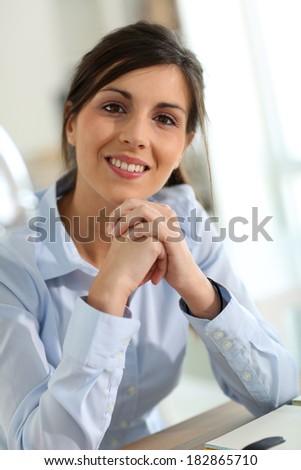 Portrait of smiling brunette woman in office