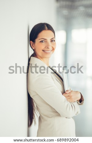Portrait of smiling business lady leaning on wall